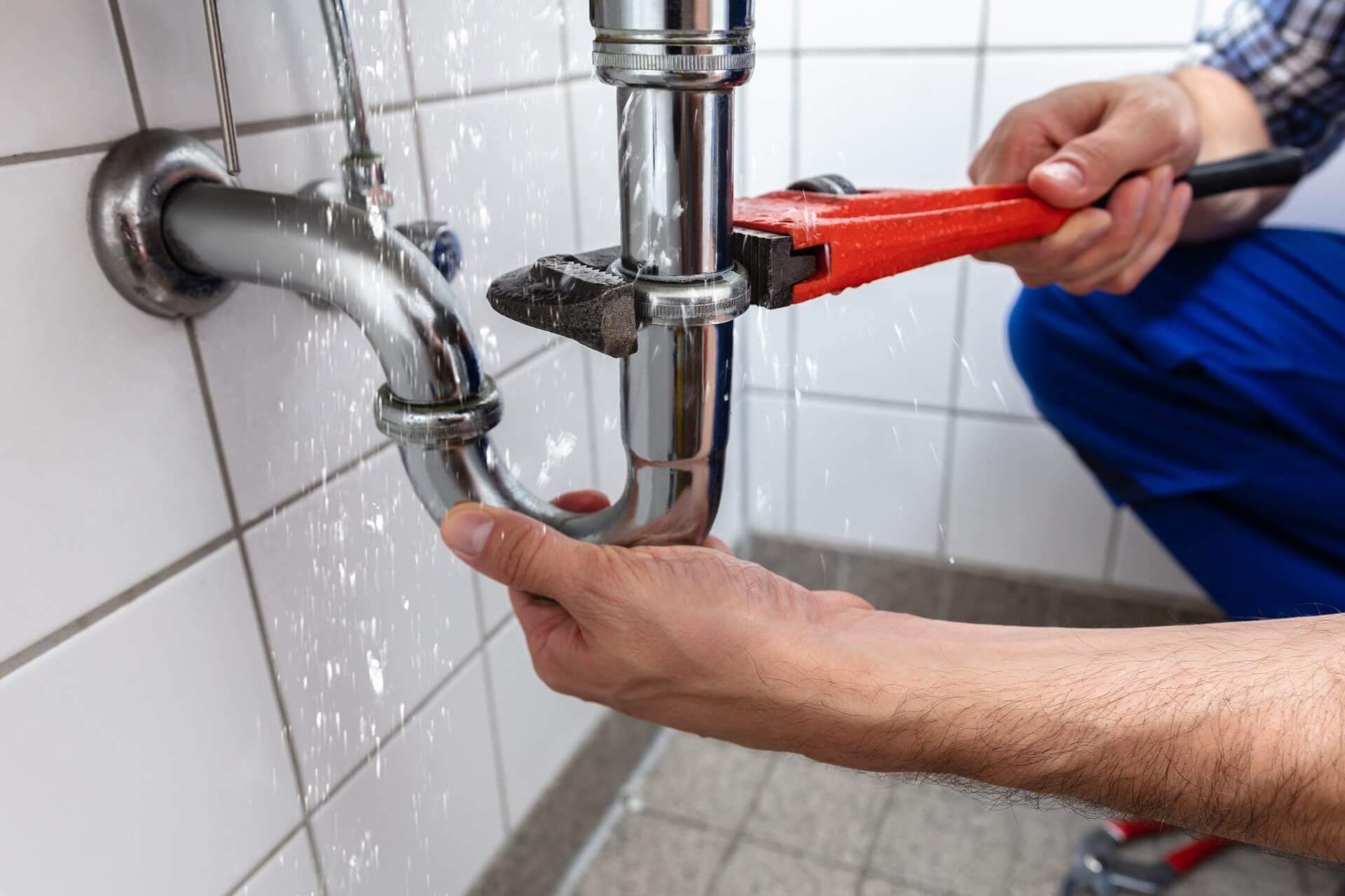 man fixing leaking pipe water restoration